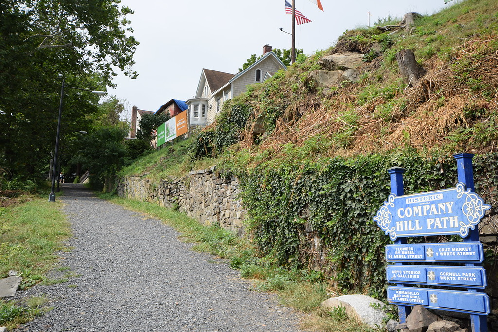 . Looking up Company Hill Path from West Strand, Kingston, N.Y.,  the proposed site of the Irish Cultural Center is above the stone wall and marked by a sign and  flags.