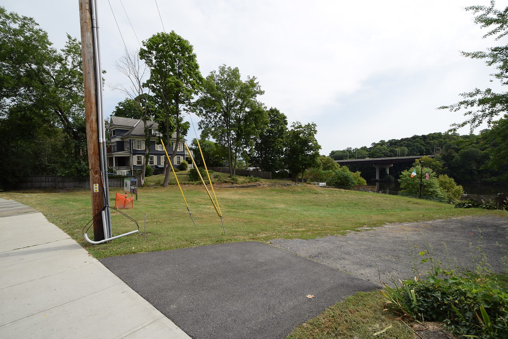 . The proposed site of the Irish Cultural Center looking from Abeel Street, Kingston, N.Y., showing a residence on an abutting property to the left and the Loughran Bridge across the Rondout Creek in the background at right.
