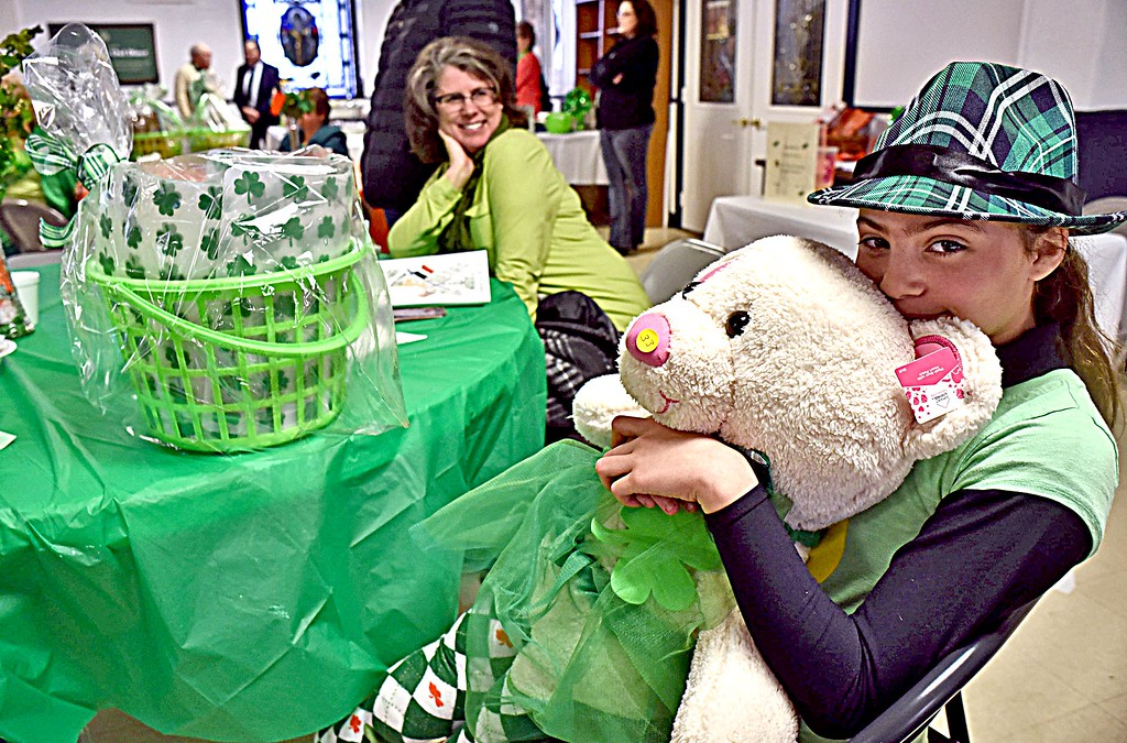 . Ahhh the luck of the Irish, 10 year old Analys Lutter of Lowell, gives a big hug to the Irish dancing bear she just won in the raffle at the Irish Cultural Week kick-off Brunch, she also won the basket on the table right before winning the bear, her mom in back is Kathleen Lutter flashes a big smile. SUN/ David H. Brow