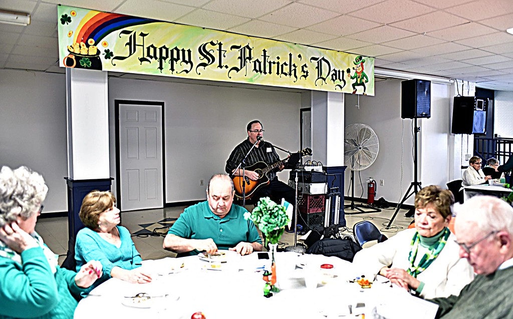 . Folks enjoying the food and music at the kick-Off Brunch for Irish Cultural Week at St Patrick\'s Church, providing music in back is Chuck Campbell. SUN/ David H. Brow