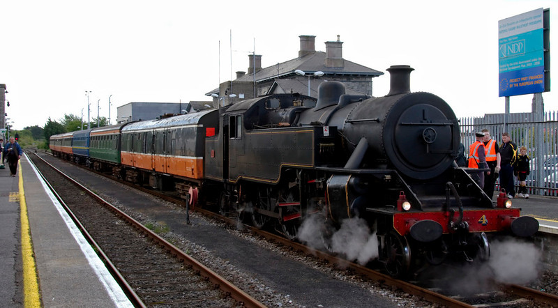 No 4, Athlone, 9 May 2009 - 1241    As can be seen, the train was formed of six coaches, all owned by the RPSI.  Behind the engine is generating steam van 3185, built in the 1950s by Gloucester RCW as a BR Mark 1 BSK.  The five coaches were all supplied to CIE in 1963-64 by Craven of Sheffield.  Blue notices such as the one seen here stood at several stations whose modernisation had been partly financed by the EU.