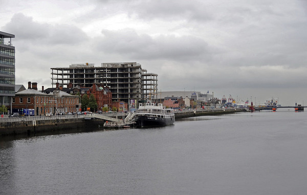 Former LNWR station and hotel, North Wall, Dublin, 10 May 2012.  Looking east along the Liffey.  The station (nearer) and hotel are the red brick buildings at left.  The North Wall quay used to be Dublin's port, from which ferries sailed to Britain.  The London & North Western Railway ran a prestige route to Holyhead, from where its trains (including the Irish Mail) ran to Euston.  Trains ran from its North Wall passenger and goods station (opened 1877) onto the Irish rail network.  The passenger station was only used for boat trains.  The hotel opened in 1884.  In 1922, Holyhead passenger services were transferred to Dun Laoghaire, although railway-owned ships continued to call at North Wall for cattle and cargo.  Other companies also continued to run passenger services from North Wall,  The hotel also closed in 1922, and has been used for offices by the LMS, CIE and Iarnrod Eireann.  The ship is the preserved Cobh tender Cill Airne (= Killarney), now a restaurant.  Today's Dublin port is at the mouth of the Liffey, where a ferry can just be seen in the far distance at right.