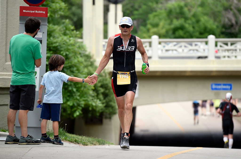 . Andrew Wrenshall high-fives Willem Seaton-Wiseman, 6, as he runs the course during the 2018 Boulder Ironman race on Sunday in Boulder. For morep photos of the race go to www.dailycamera.com Jeremy Papasso/ Staff Photographer 06/10/2018