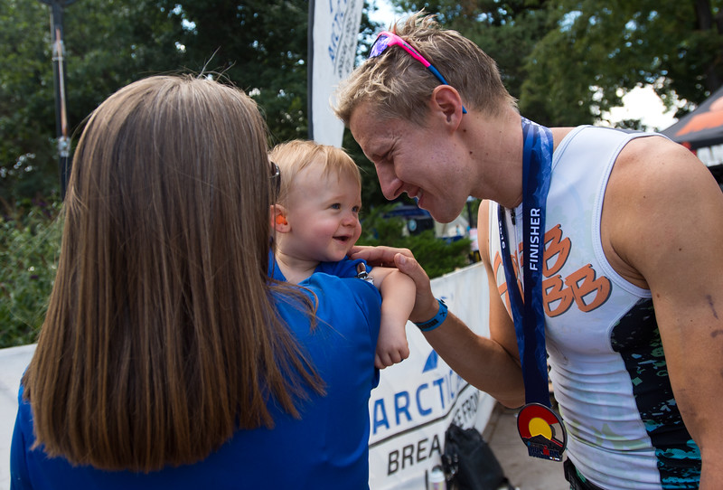 """Clay Emge, of Tyler, Texas, who finished first place overall in the 2016 Ironman Boulder, greets his child Jordan Emge and his wife, Kimberly Emge, after the race on Sunday. <br /> More photos:  <a href=""""http://www.dailycamera.com"""">http://www.dailycamera.com</a><br /> (Autumn Parry/Staff Photographer)<br /> August 7, 2016"""
