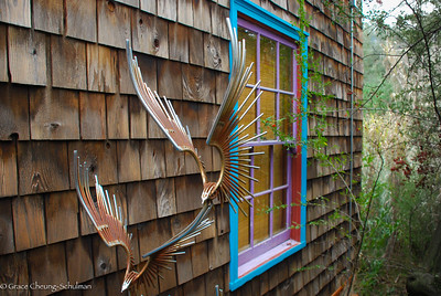 The rusted iron sculpture frames the brightly painted window of the Lodge.
