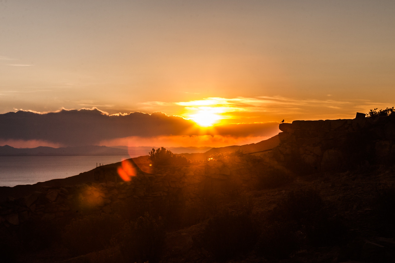 Sun setting over the Peruvian mountains over the horizon seen from Isla del Sol, in Lake Titicaca, Bolivia