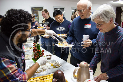 Mutlaq Alqahtani, freshman in physics, serves baklava to members of the Manhattan, Kansas community at the Islamic Center's annual open house. (Regan Tokos | The Collegian)