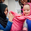At left, Adiva Daniar of Chelmsford teaches Ciara McComiskey, 6, of Andover how to put on a hijab at the open house for Islamic Society of Greater Lowell. SUN/Caley McGuane
