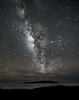Milky Way seen above Mauna Loa peeking through the cloud cover on the Big Island of Hawaii.  The image was taken from Mauna Kea at 12,800 foot elevation.