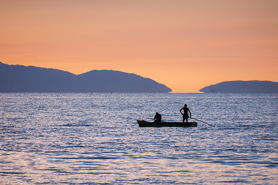 Two men take a leisurely evening drift just off the Waterloo shoreline at sunset. The hills in the distant are the small islands off the north-western tip of Trinidad.