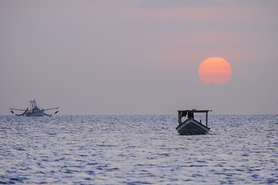Fishing boats sit on calm seas at sunset off of Trinidad's West Coast.