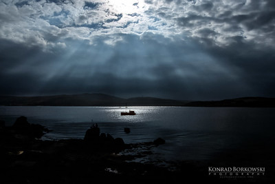 Light breaking through the clouds over a fishing boat in Kilnaughton Bay, Port Ellen, Isle of Islay