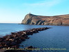 Remains of the Port Erin outer breakwater constructed in 1863 and destroyed in a storm during 1884. Bradda Head can be seen in the background. On the beach below the head can be seen the chimney and engine house of Bradda Head Mine. Above on the headland is Milner's Tower.