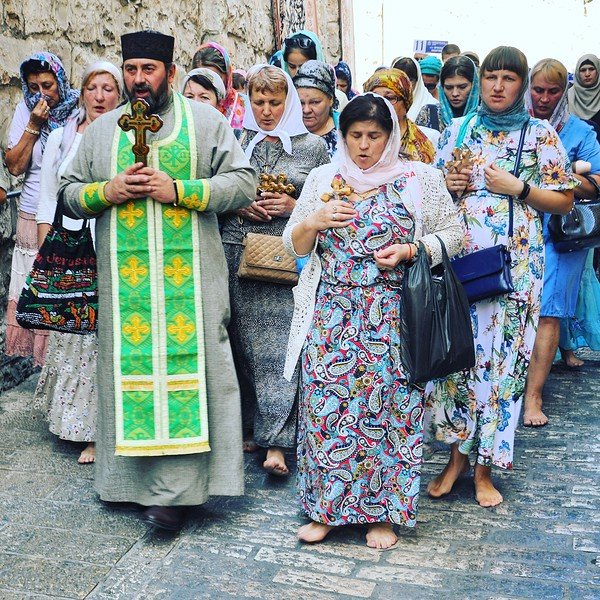 Christian pilgrims walk barefoot along the Via Dolorosa. 2016.