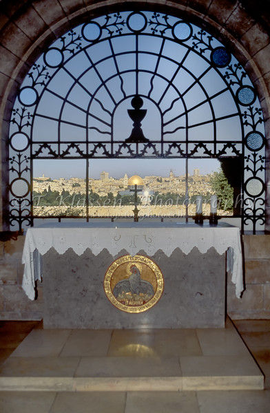 A church window overlooking the skyline of Jerusalem in the Dominus Flevit Roman Catholic Church on the Mount of Olives in Jerusalem, Israel, USA.