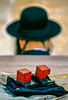 A set of tefillin boxes on a table with the hat of an Orthodox Jewish man at the Western Wall in Jerusalem, Israel.
