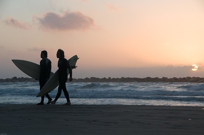 Tel Aviv surfers at sunset