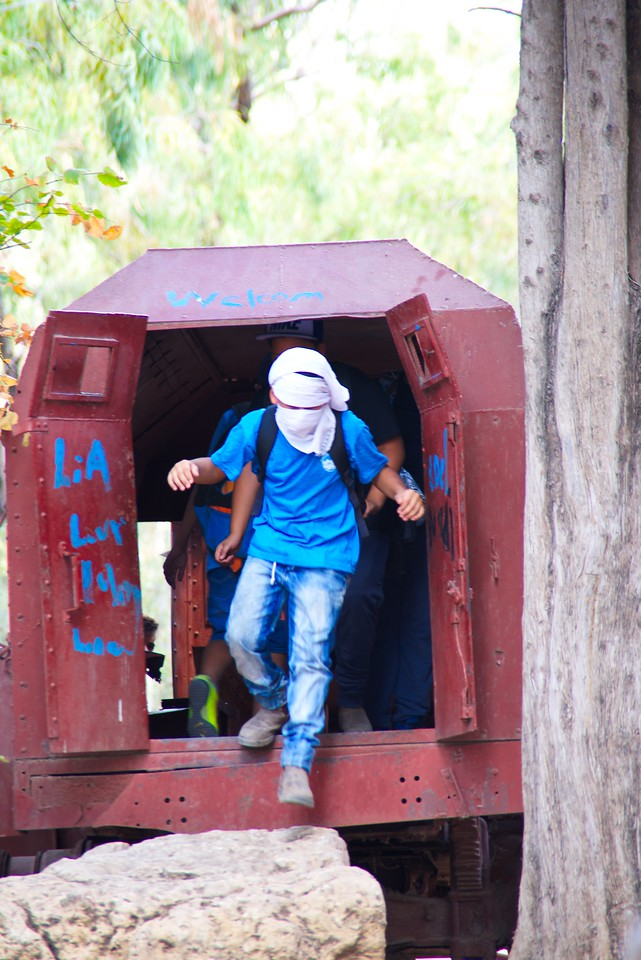 Muslim boys playing on the burned out armored bus.