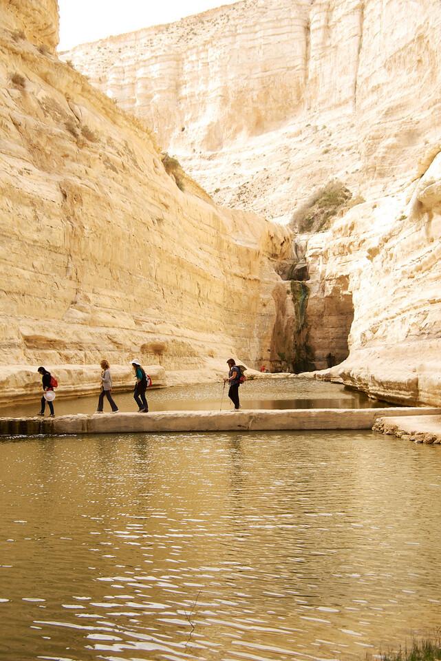 People Crossing Dam on Way to Waterfall