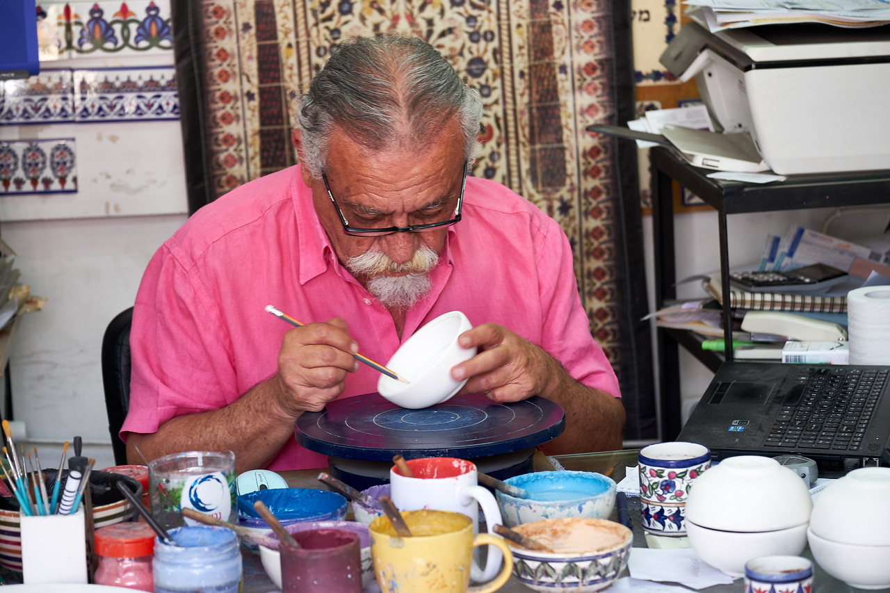 Hand painting Jerusalem pottery.