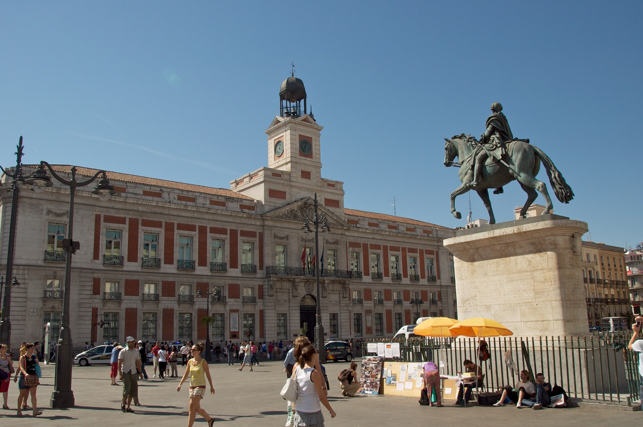 "Puerta del Sol… Statue of Charles III, ""The Greatest Mayor"" (left) and the Old Post Office Now The Office of The President of Spain…The Times Square of Madrid…Large Gathering for New Year's Eve"