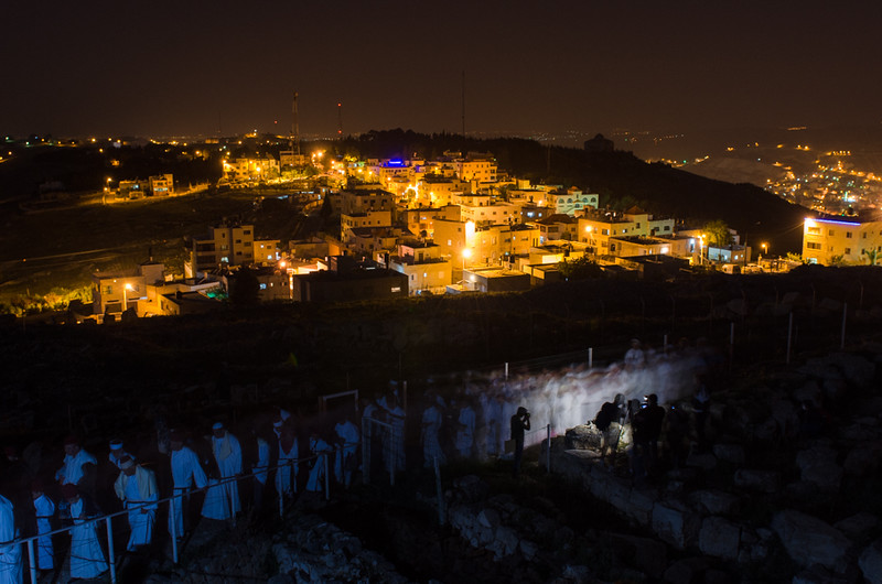 Samaritans are making the pilgrimage from the synagogue to the Temple Mount on Mt Gerizim.  On the middle of the photo is the Samaritan town of Kiryat Luza. On the upper right part of the photo is the Palestinian refugee camp, Balata.  Balata was once the largest refugee camp on the West Bank and is adjacent to Nablus.