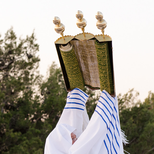 The Samaritan Torah is being waved in its scroll case. Three pomegranates are located on top of each section of the scroll case.  The three pomegranates represent Abraham, Isaac and Jacob.  When the scroll case is closed it symbolizes the tree of life. The head cantor is wearing an additional tallit called a tzitzit-tallit, which is similar to a Jewish tallit. When the head cantor waves the Torah, it represents Abraham waving the sheep prior to sacrificing it.