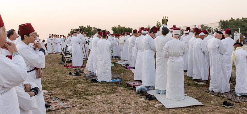 All men are wearing virtually identical Samaritan tallit, lengthy white garments made of simple cotton, representing that all men are equal under G-d. <br /> <br /> Shoes are removed for prayer and placed behind the prayer mat.  Shoes are removed because when G-d exposed himself to Moses, he told Moses to take off his shoes because the ground was sacred. <br /> <br /> The Torah is held high and waved three or four times at each of the seven prayer stations.