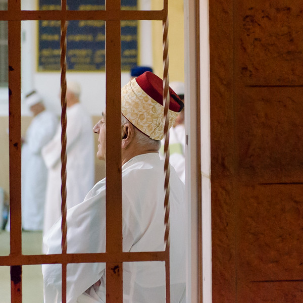The white garment is a tallit. Tallit are worn on Festivals and Shabbat. The head covering is a tarbush (turban). Priests wear white turbans with red tops. When the white material is patterned, the tarbush signifies that the priest is also an elder, the oldest male in his family. During the week, priests wear all-red turbans.