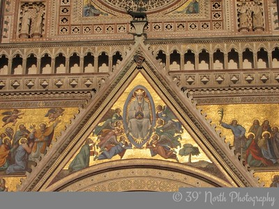 The mosaic over the main portal depicts the Assumption of Mary, designed by Giovanni di Buccio Leonardelli in 1366. Six angels lift the mandorla; Saint Thomas is at the left with the belt of the Virgin. The famous doubter had asked for a sign she had really ascended