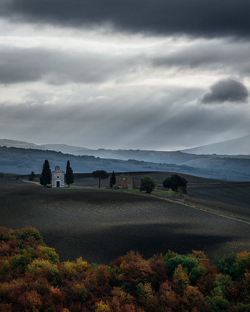 Moody light above a Tuscan home and fall foliage in Val D'orcia - Tuscany