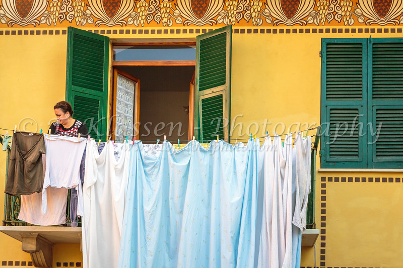 A lady hanging out laundry to dry in the village of Corniglia, Cinque terre, Italy, Europe.