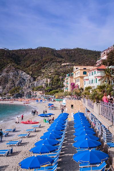 The sandy beach with blue umbrellas in Monterosso al Mare, Liguria, Italy, Europe.