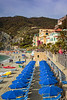 The sandy beach with blue umbrellas in Monterosso al Mare, Liguria, Italy, Europe.