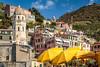 Yellow umbrellas at a portside restaurant in the village of Vernazza, Cinque Terre, Liguria, Italy, Europe.