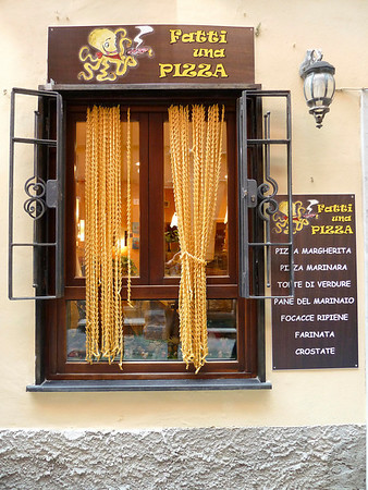 Restaurant with pasta strung together to make curtains.