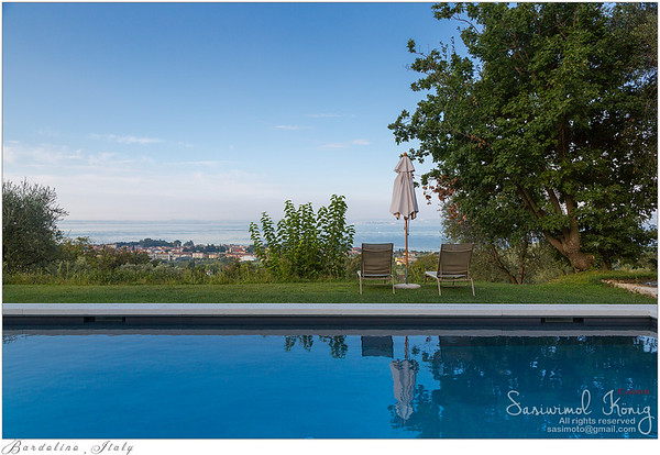 Swimming pool area in the morning with beautiful view of Garda lake