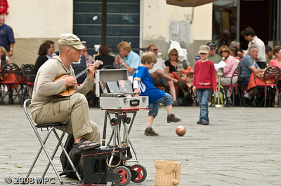 Musician and kids playing football the Piazza Anfiteatro Romano