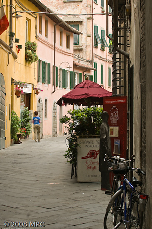 Via (street) leading to the Piazza Anfiteatro Romano.  Bicycles are the most popular way to get around in Lucca.