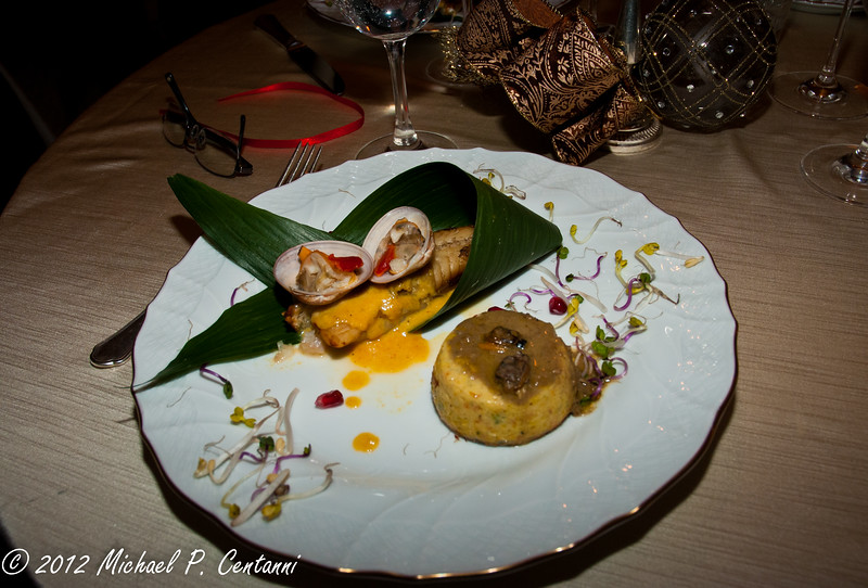 Monkfish fillets with citrus and tropical fruit and clams cooked on banana leaves and timbale of nettle in a clam sauce