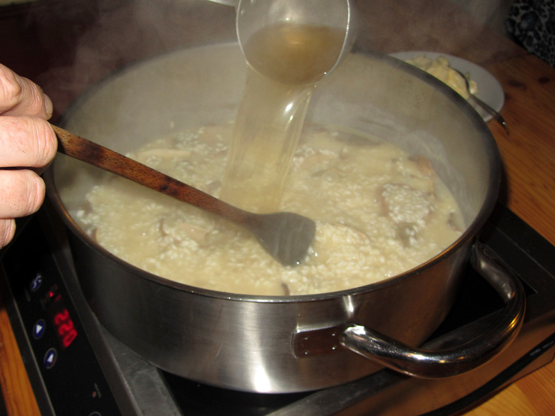 adding beef stock to the risotto