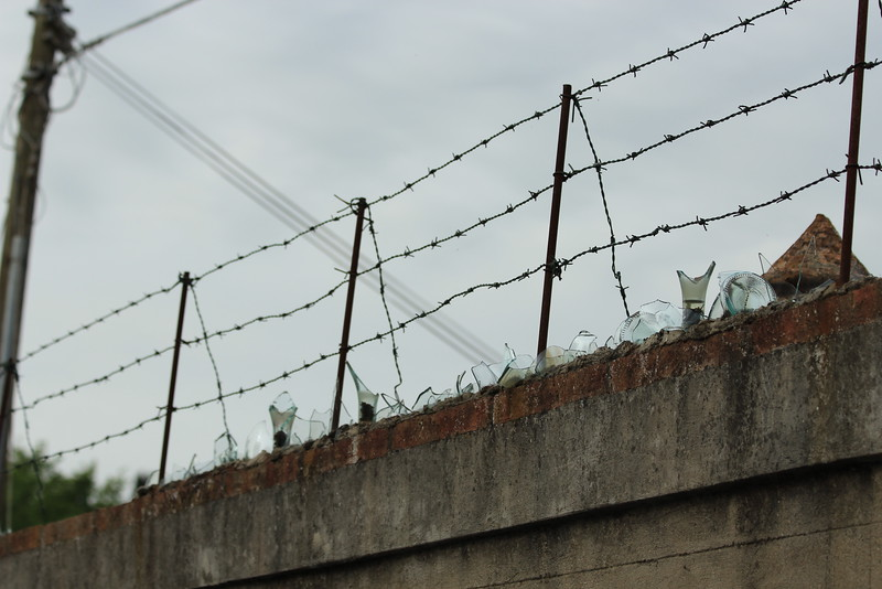 Security fence with glass and barbed wire, Florence, Italy