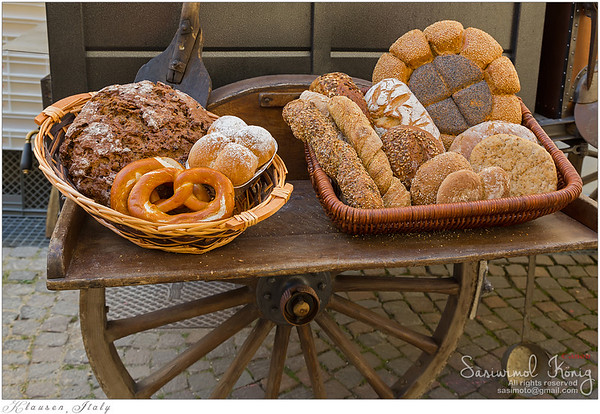 Basket of freshly baked bread in front of portable wood fired oven