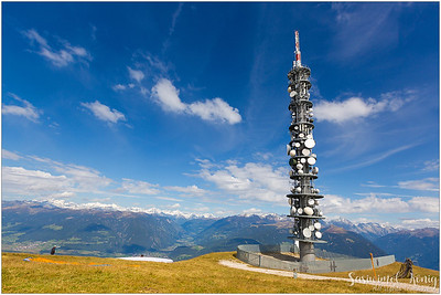Telecommunication tower on top of the mountain. A paraglider is about to take off?