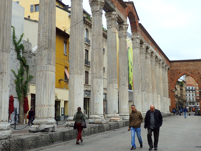 People walking nearby Colonne di San Lorenzo Roman Ruins in Milan, Italy