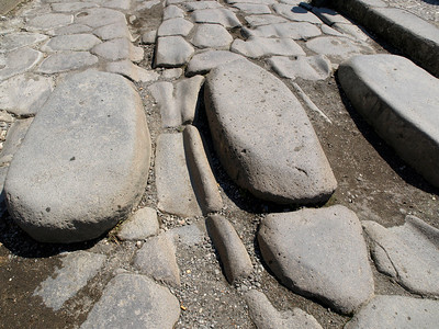 Pompeii - Ruts in paving stones from carts. Taller stones are for pedistrians to step over water and sewage in streets.