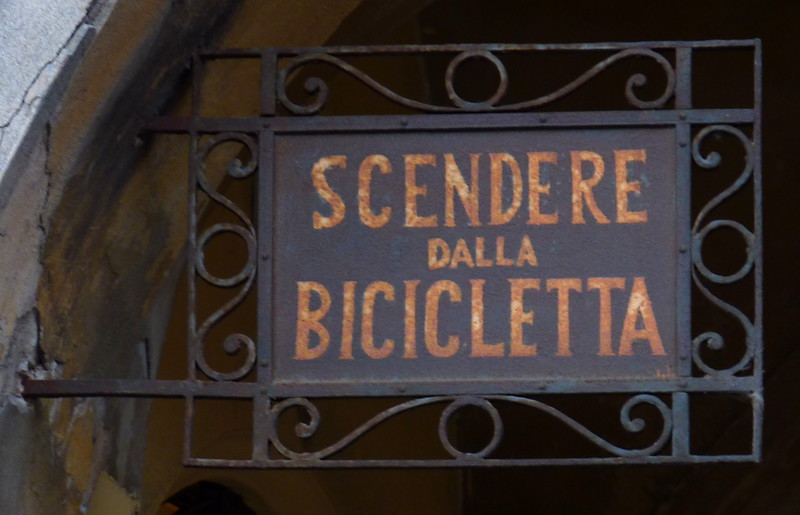 "Piazza Duomo; scendere dalla bicicletta.<br /> <br /> The sign says ""Dismount bike""."