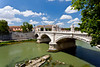 The city skyline with churches and a bridge over the Tiber River in Rome, Italy.