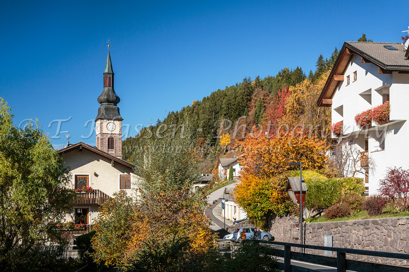 The Parish church of St. Peter in the village of San Pietro with fall foliage color in Val di Funes, South Tyrol, Italy, Europe.