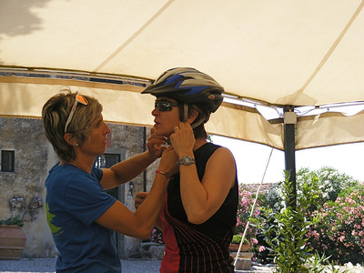First day of cycling, Elena helps adjust a helmet.